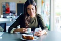 Mooi meisje die haar mobiele telefoon in koffie met behulp van Stock Foto