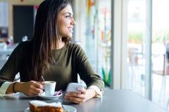 Mooi meisje die haar mobiele telefoon in koffie met behulp van Stock Fotografie
