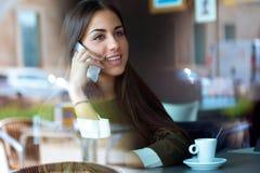 Mooi meisje die haar mobiele telefoon in koffie met behulp van Royalty-vrije Stock Afbeelding