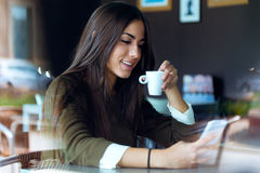 Mooi meisje die haar mobiele telefoon in koffie met behulp van Stock Afbeeldingen