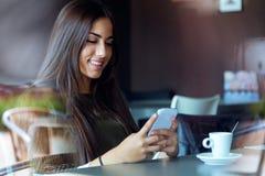 Mooi meisje die haar mobiele telefoon in koffie met behulp van Royalty-vrije Stock Foto