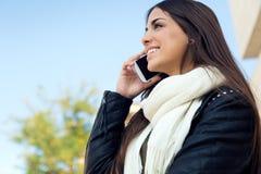 Mooi meisje die haar mobiele telefoon in stad met behulp van Stock Foto