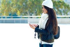 Mooi meisje die haar mobiele telefoon in stad met behulp van Stock Afbeelding