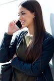 Mooi meisje die haar mobiele telefoon in stad met behulp van Stock Fotografie