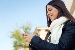 Mooi meisje die haar mobiele telefoon in stad met behulp van Royalty-vrije Stock Foto