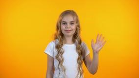 Mooi meisje die hello, glimlachen vriendschappelijk aan camera, gelukkige kinderjaren golven stock video