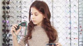 Mooi meisje die het verwarde kiezen tussen twee paren zonnebril kijken stock video