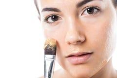 mooi meisje die honingsmasker op gezicht met borstel toepassen stock fotografie