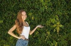 Mooi meisje die houdend een palm met exemplaarruimte aanbieden royalty-vrije stock afbeelding