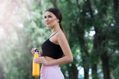 Mooi meisje die klaar voor jogging in het park worden Met thermosflessenfles ter beschikking stock foto's