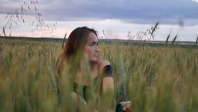 Mooi meisje die in kleding binnen door gebied wat betreft tarweoren bij zonsondergang lopen stock videobeelden