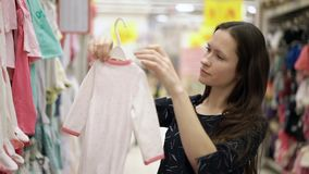Mooi meisje die kleren voor de baby kiezen die zich dichtbij een plank van de kleren van kinderen in supermarkt, het winkelen, wa stock footage