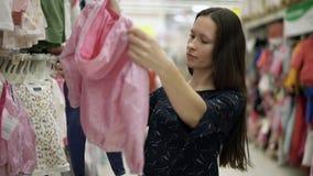 Mooi meisje die kleren voor de baby kiezen die zich dichtbij een plank van de kleren van kinderen in supermarkt, het winkelen, wa stock videobeelden