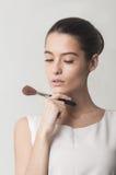 Mooi meisje die kosmetische borstel houden Stock Fotografie