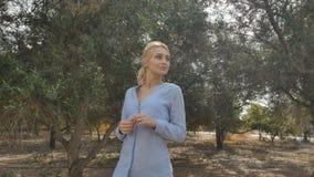 Mooi meisje die langs de aanplanting met olijfbomen lopen stock videobeelden
