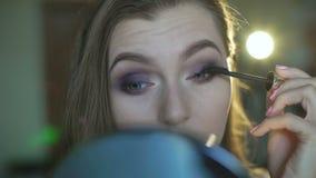 Mooi meisje die mascara op wimpers 4K toepassen stock video