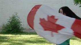 Mooi meisje die met een vlag van Canada dansen stock videobeelden