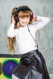 Mooi meisje die met hoofdtelefoons aan de radio luisteren Co Stock Afbeeldingen