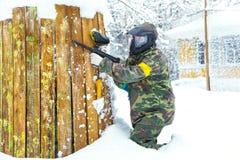 Mooi meisje die met luchtkanon paintball in de winter spelen Royalty-vrije Stock Foto
