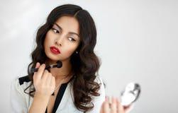 Mooi meisje die met perfecte huid make-up toepassen stock afbeelding
