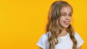 Mooi meisje die naar camera op ge?soleerde gele achtergrond, malplaatje knipogen stock video