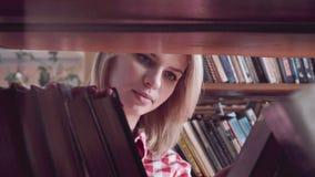 Mooi meisje die naar een boek zoeken stock footage