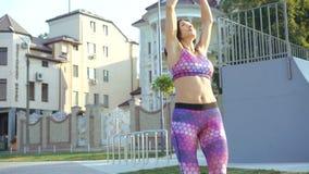Mooi meisje die oefening met flexibiliteit openlucht in 4K doen stock video