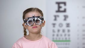 Mooi meisje die ogen met phoropter in kinderen oftalmologische kliniek onderzoeken stock video