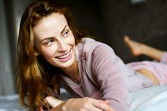 Mooi meisje die op bed glimlachen Stock Afbeelding