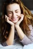 Mooi meisje die op bed glimlachen Stock Foto's