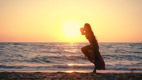 Mooi meisje die op de overzeese kust bij zonsopgang springen
