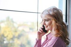 Mooi meisje die op de telefoon dichtbij een venster spreken Bedrijfs concept royalty-vrije stock foto