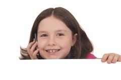 Mooi meisje die op een mobiele telefoon achter exemplaar spreken spac Stock Fotografie