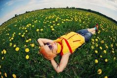 Mooi meisje die op een weide in een gebied van bloemen, paardebloemen liggen Stock Afbeelding