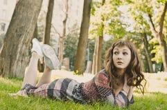 Mooi meisje die op het gras in het park liggen Stock Foto's