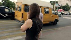 Mooi meisje die op Smartphone bij straatzebrapad spreken stock video