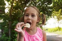 Mooi meisje die pret hebben in openlucht De baby zet chips in zijn mond Slecht voedsel Jungvoedsel, royalty-vrije stock foto's