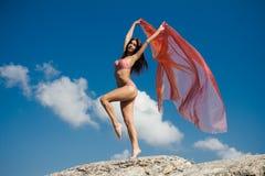 Mooi meisje die roze doek in wind met hemel houden Royalty-vrije Stock Afbeelding