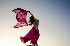 Mooi meisje die roze doek in wind met hemel houden Royalty-vrije Stock Fotografie