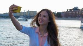 Mooi meisje die selfie zitting op de waterkant van de stad doen stock videobeelden