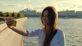 Mooi meisje die selfie zitting op de waterkant van de stad doen stock footage