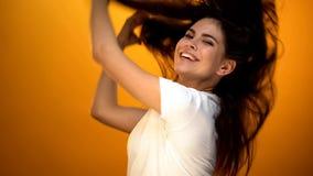 Mooi meisje die terug haar werpen en aan camera glimlachen, die van het gelukkige leven genieten stock foto's