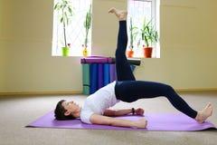 Mooi meisje die uitrekkende oefeningen en yogaasanas doen stock afbeelding