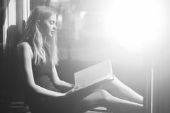 Mooi meisje die verhaal met leeg boek veronderstellen bij open venster stock foto's