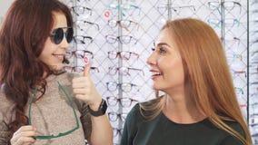 Mooi meisje die voor zonnebril met haar mooie moeder winkelen royalty-vrije stock afbeelding