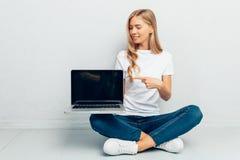 Mooi meisje die witte t-shirt dragen die lege laptop het schermzitting op vloer op grijze achtergrond tonen stock fotografie