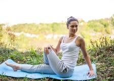 Mooi meisje die yogaoefeningen op het tapijt in aard doen Royalty-vrije Stock Foto