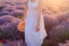 Mooi meisje die zich in de hoed van de holdingsfedora van het lavendelgebied in haar hand bevinden stock afbeeldingen