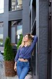 Mooi meisje die zich dichtbij de bouw en groene installatie bevinden Stock Foto's