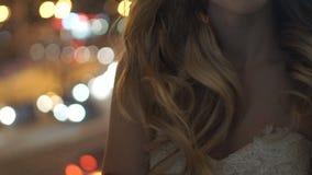 Mooi meisje die zich dichtbij een venster in de avond bevinden stock footage